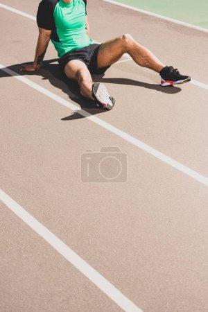 Photo pour Vue recadrée du sportif fatigué s'asseyant au stade - image libre de droit
