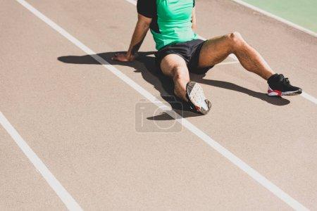 Photo pour Vue partielle du sportif de course mélangé s'asseyant au stade - image libre de droit