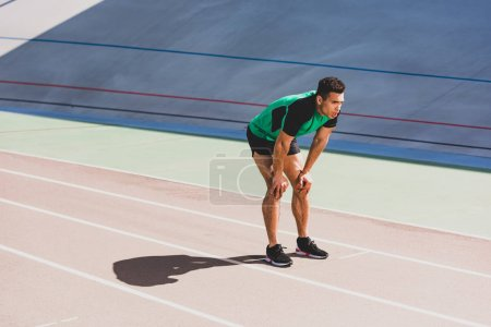 Photo for Tired mixed race sportsman in sportswear standing at stadium with hands on knees - Royalty Free Image