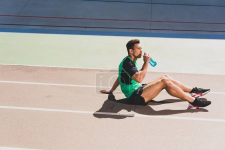 Photo for Mixed race sportsman sitting at stadium and drinking water - Royalty Free Image