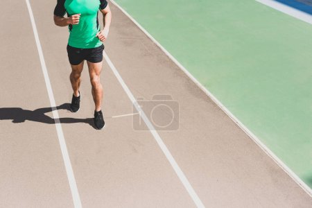 Photo for Cropped view of sportsman in sportswear running at stadium - Royalty Free Image
