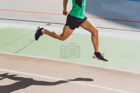 Photo for Cropped view of sportsman in black sneakers running at stadium - Royalty Free Image
