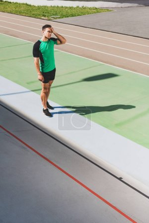 Photo for Full length view of tired mixed race sportsman standing at stadium - Royalty Free Image