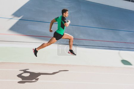 Photo for Full length view of mixed race sportsman running at stadium - Royalty Free Image