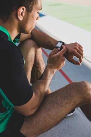 Photo for Cropped view of mixed race sportsman using smartwatch at stadium - Royalty Free Image