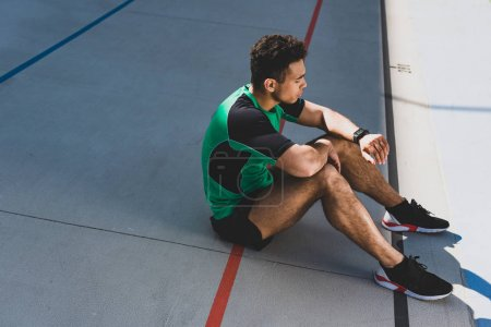 Photo for Handsome mixed race sportsman sitting on running track and looking at smartwatch - Royalty Free Image