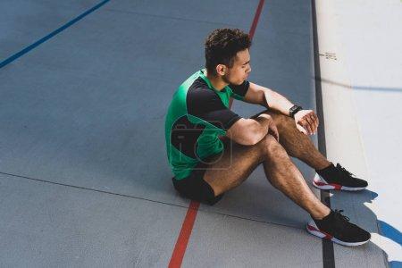 Photo pour Beau sportif de course mixte assis sur la piste de course et en regardant smartwatch - image libre de droit