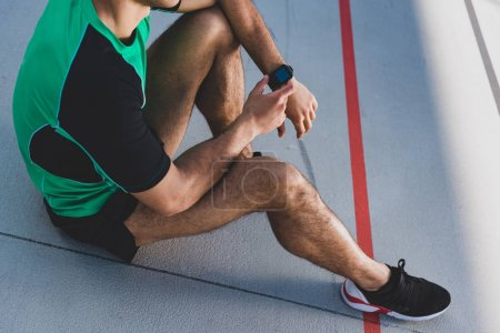 Photo for Cropped view of mixed race sportsman using smartwatch at running track - Royalty Free Image