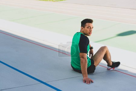 Photo for Handsome mixed race sportsman sitting on running track and looking at camera - Royalty Free Image