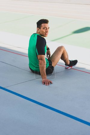 Photo for Handsome mixed race sportsman sitting on running track, smiling and looking at camera - Royalty Free Image