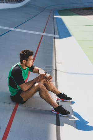 Photo for Handsome mixed race sportsman sitting on running track at stadium and looking at smartwatch - Royalty Free Image