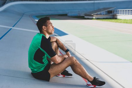 Photo for Mixed race sportsman sitting on running track and looking away at stadium - Royalty Free Image