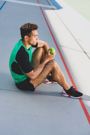 Photo for Mixed race sportsman sitting on running track and holding green apple - Royalty Free Image