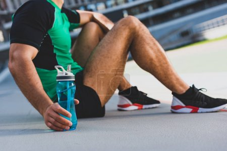 Photo for Cropped view of sportsman sitting on running track and holding bottle with water - Royalty Free Image