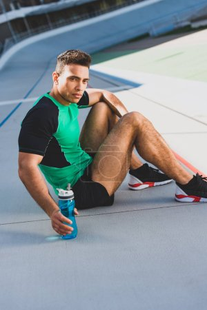 Photo for Mixed race sportsman sitting on running track, seriously looking at camera and holding bottle with water - Royalty Free Image