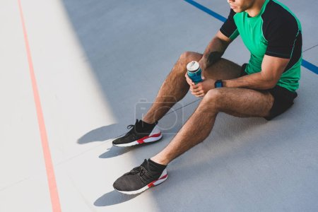Photo for Cropped view of sportsman sitting on running track and holding blue bottle with water - Royalty Free Image