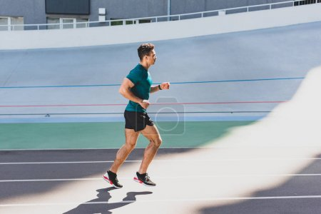 Photo for Side view of mixed race sportsman running on track at stadium - Royalty Free Image