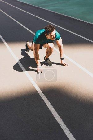 Photo pour Beau sportif de course mixte sur la position de départ regardant loin au stade - image libre de droit