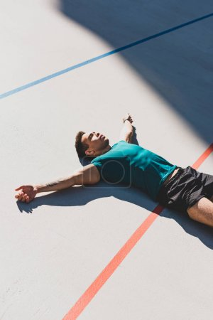 Photo for Mixed race sportsman laying on running track and spread arms - Royalty Free Image