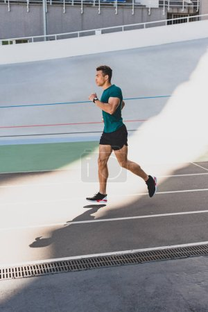 Photo for Side view of mixed race sportsman jogging on running track - Royalty Free Image