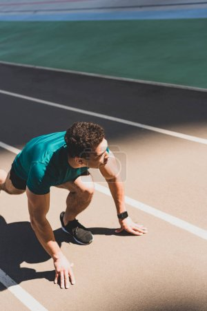 mixed race sportsman on start position on running track, looking away at stadium