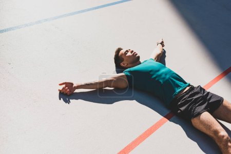 Photo for Mixed race sportsman laying on running track and spread arms in sunlight - Royalty Free Image