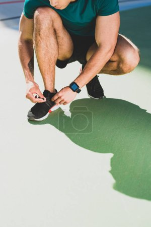 Photo for Cropped view of sportsman lacing up sneakers at stadium - Royalty Free Image