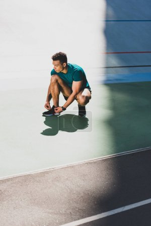 Photo for Mixed race sportsman lacing up sneakers at stadium - Royalty Free Image