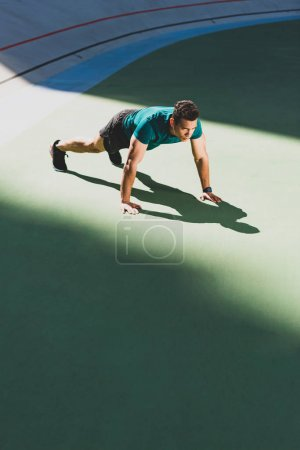 Photo for Mixed race sportsman pressing up at stadium - Royalty Free Image