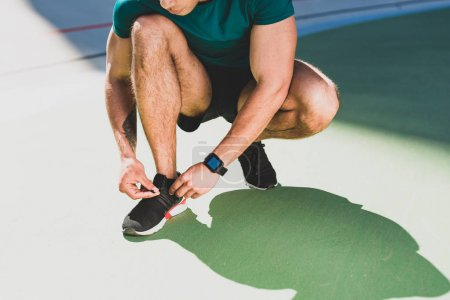 Photo for Cropped view of sportsman lacing up sneakers, standing on green floor - Royalty Free Image