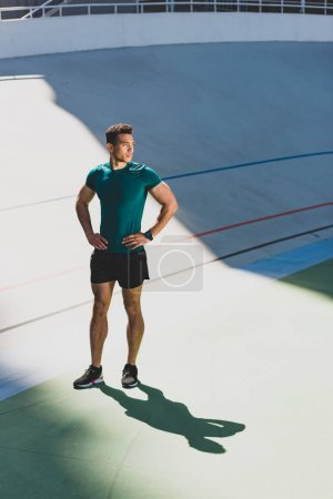 Photo for Mixed race sportsman standing with hands on hips at stadium - Royalty Free Image