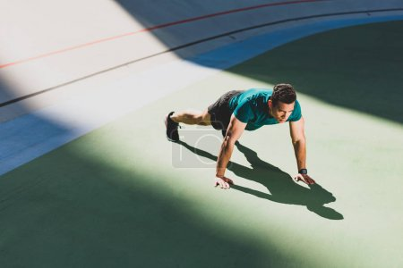 Photo for Mixed race sportsman pressing-up at stadium in light place - Royalty Free Image