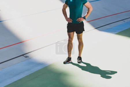Photo for Cropped view of sportsman standing with hands on hips at stadium - Royalty Free Image