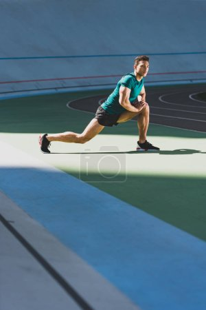 Photo for Mixed race sportsman doing lunges at stadium, standing on green floor in sunlight - Royalty Free Image