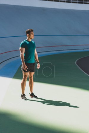 Photo for Full length view of mixed race sportsman standing in light place at stadium - Royalty Free Image