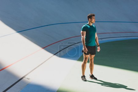 Photo for Mixed race sportsman standing in light place at stadium near running track - Royalty Free Image