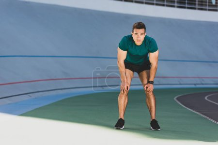 Photo for Front view of mixed race sportsman with hands on knees standing at stadium - Royalty Free Image