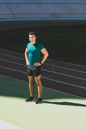 Photo for Mixed race sportsman standing with hands on hips at stadium and looking at camera - Royalty Free Image