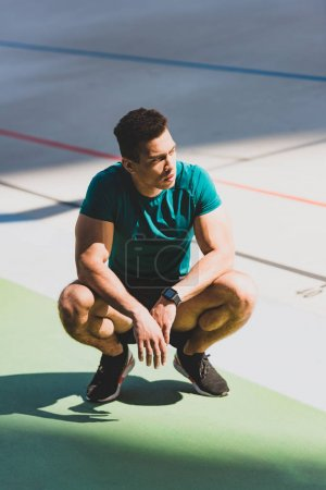 Photo for Muscular mixed race sportsman squatting at stadium in sunlight - Royalty Free Image