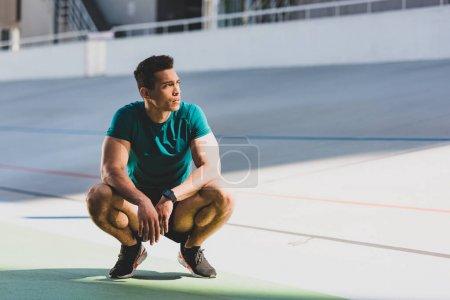 Photo pour Vue avant du sportif de course mixte accroupi et regardant loin au stade dans la lumière du soleil - image libre de droit