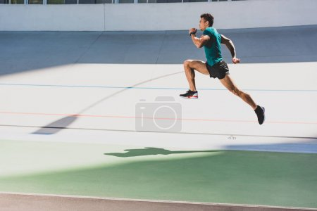 Photo for Side view of mixed race sportsman running at stadium - Royalty Free Image