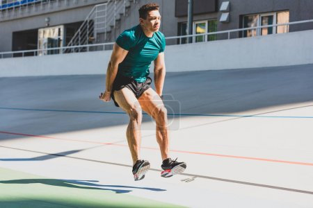 Photo for Mixed race sportsman doing long jump at stadium in sunlight - Royalty Free Image