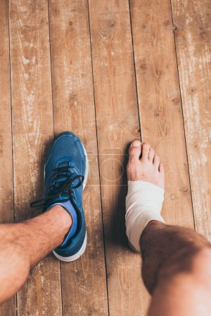 Photo for Partial view of injured sportsman sitting in one sneaker with one foot in elastic bandage - Royalty Free Image
