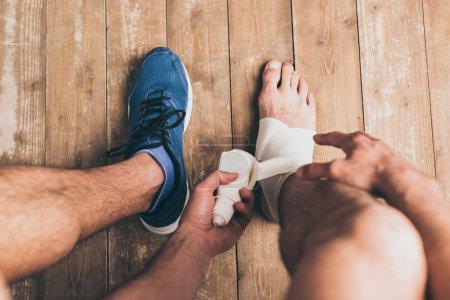 Photo pour Vue recadrée du sportif dans une chaussure bandage jambe blessée avec bandage élastique - image libre de droit
