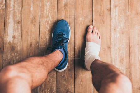 Photo for Cropped shot of injured sportsman sitting in one sneaker with one foot in elastic bandage - Royalty Free Image