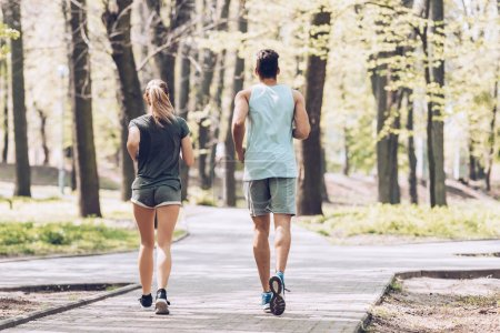 Photo for Back view of young sportsman and sportswoman running on walkway in park - Royalty Free Image