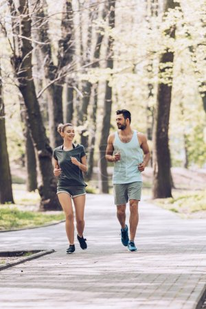 Photo pour Young man and woman in sportswear smiling while jogging in green park - image libre de droit