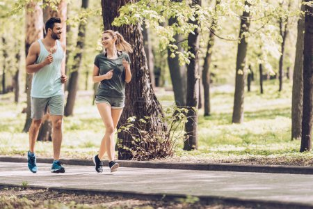 Photo for Handsome man and attractive woman talking while running in park - Royalty Free Image