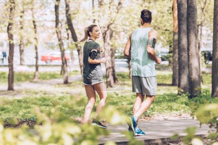 Foto de Young man and woman talking while jogging together in sunny park - Imagen libre de derechos