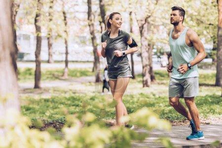 enfoque selectivo de la mujer sonriente y hombre guapo trotando en el parque